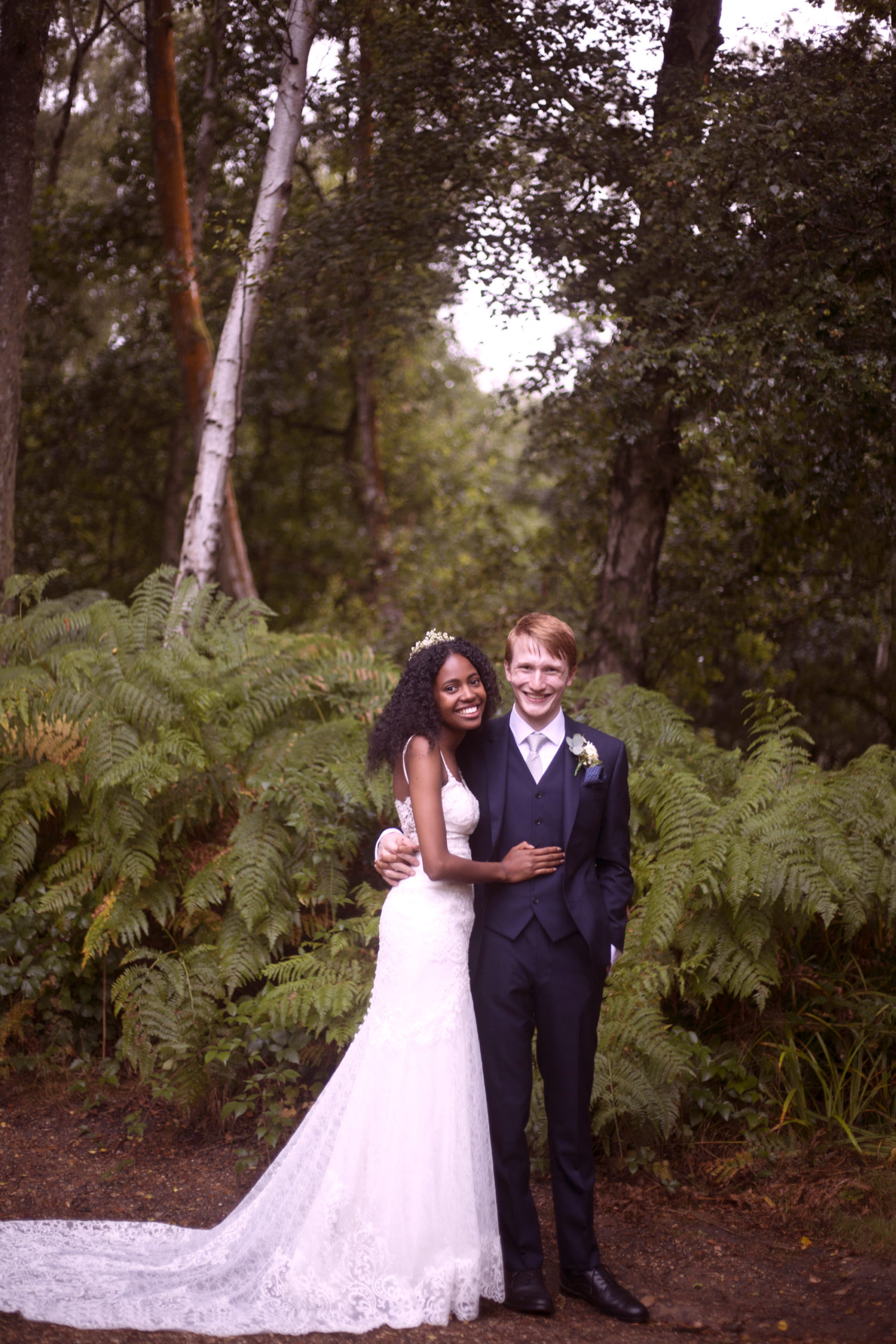 Bride and groom smile with a fern background at Cuffley camp outdoor woodland wedding photographer