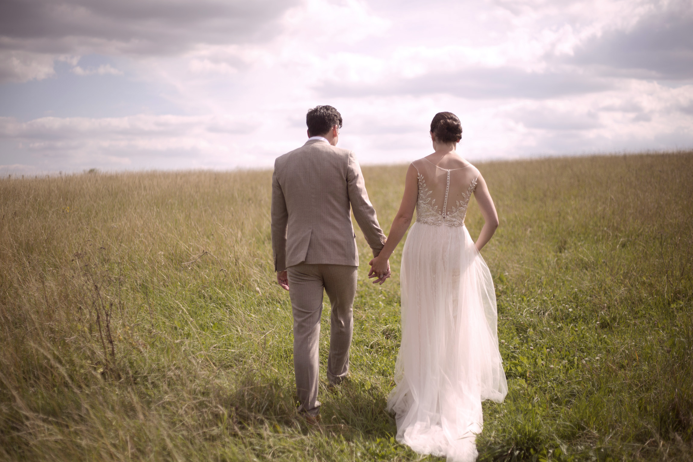 Newlyweds holding hands walking in a field at Cripps barn wedding photographer Gloucestershire