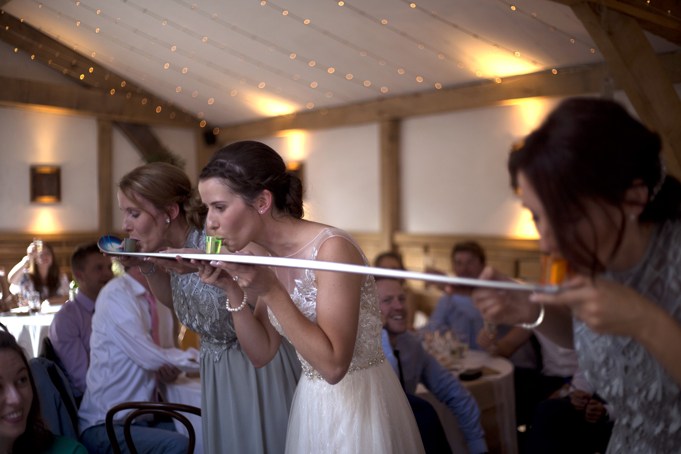 Bride does shots with her bridesmaids Cripps barn outdoor wedding photographer