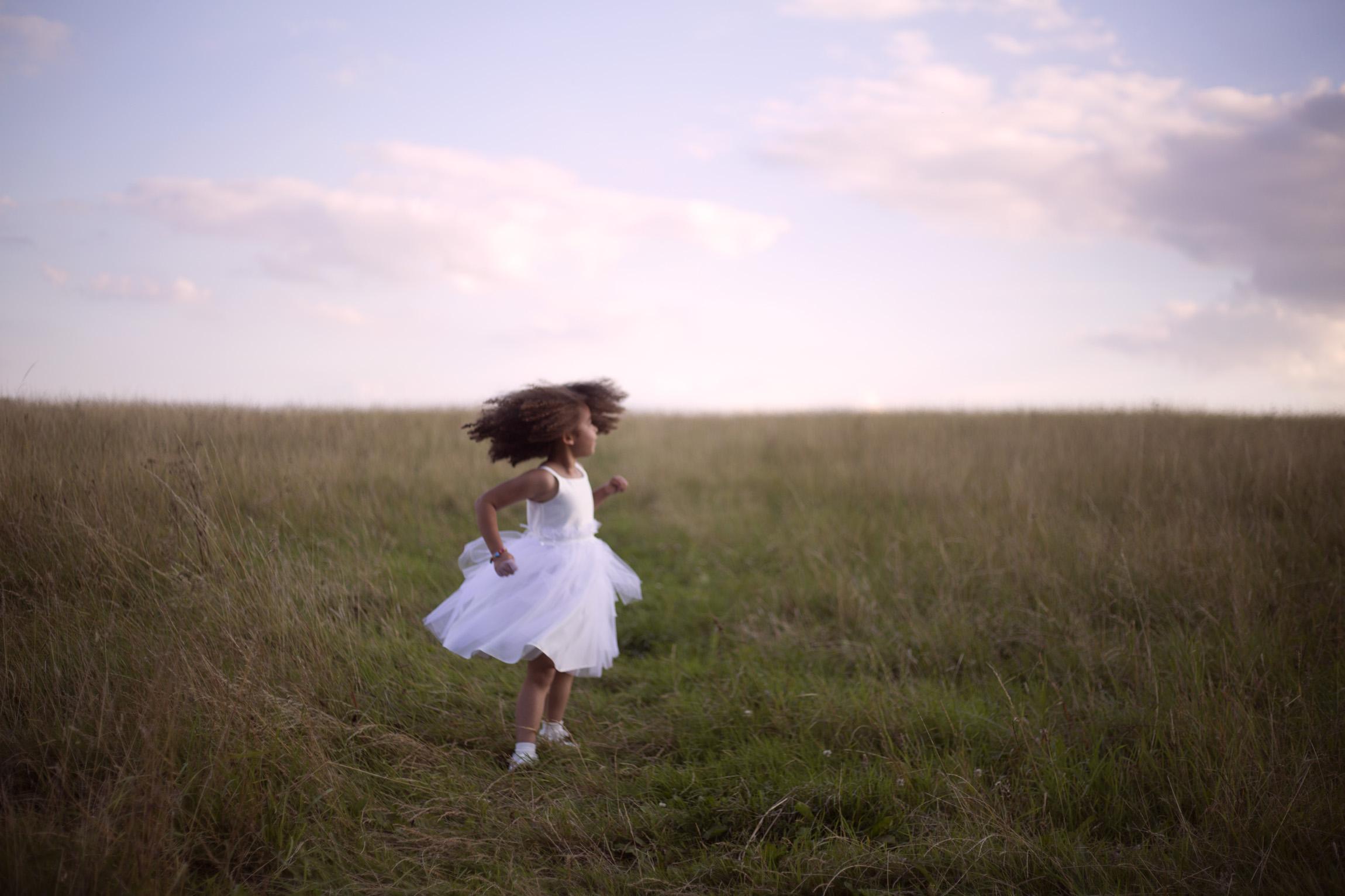 Flower girl dances in a field Cripps barn outdoor wedding photographer