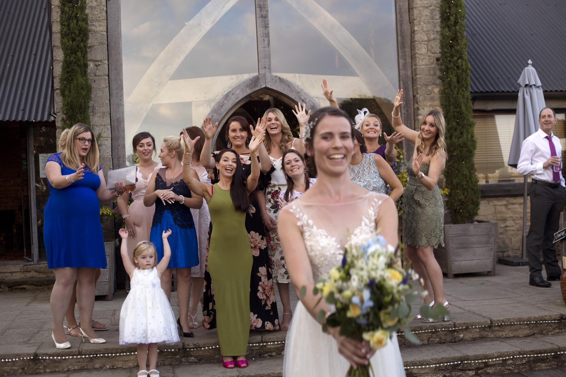 Bride throwing the bouquet Cripps barn outdoor wedding photographer