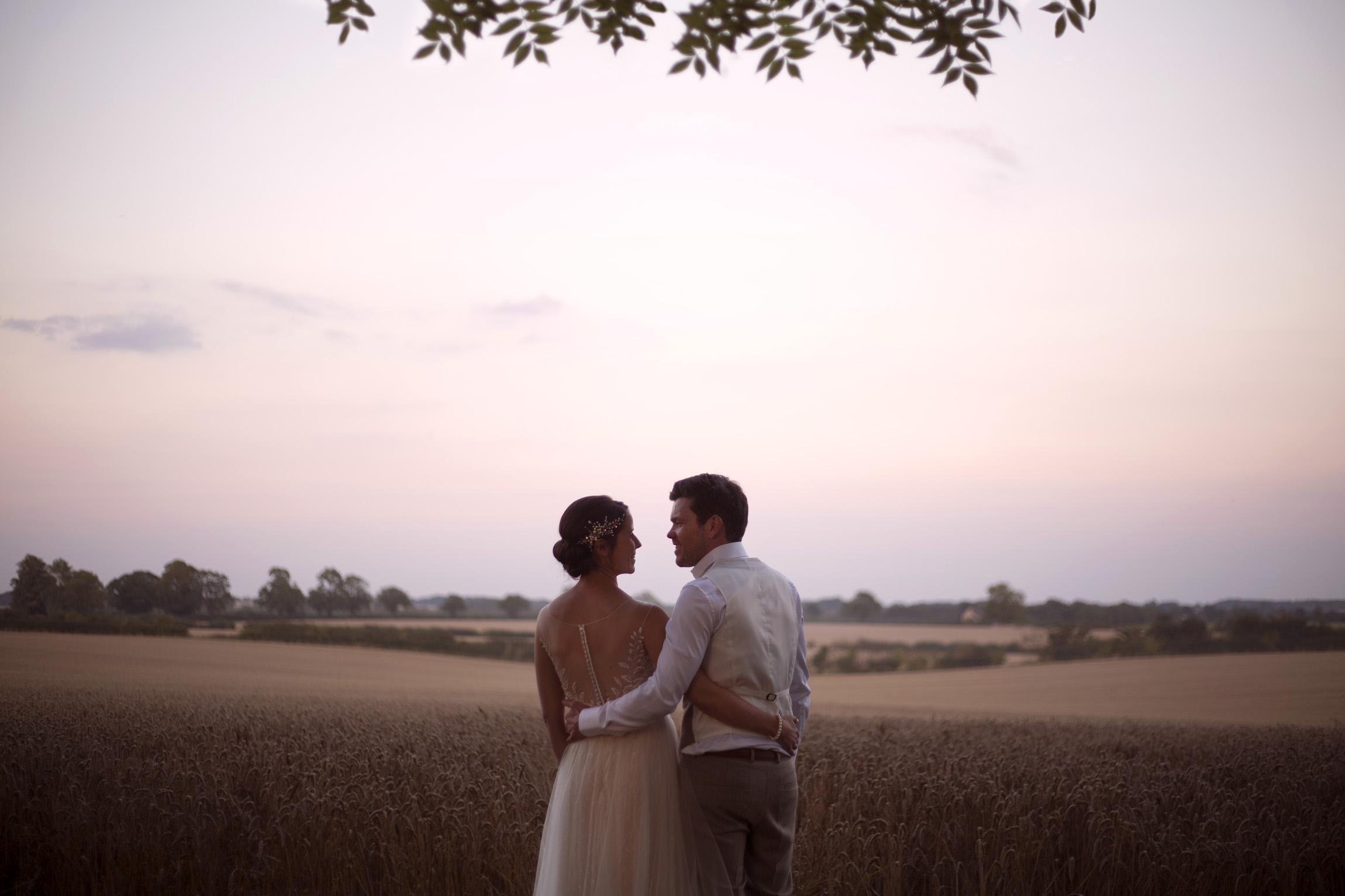 Embracing bride and groom portrait shoot in cornfield Cripps barn outdoor wedding photographer