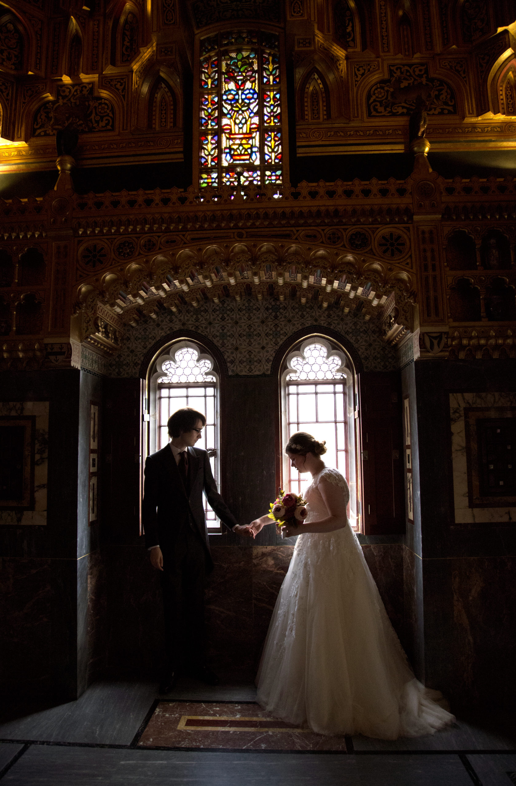 Bride and groom hold hands in Arab room Cardiff Castle Wedding Photographer St Teilos