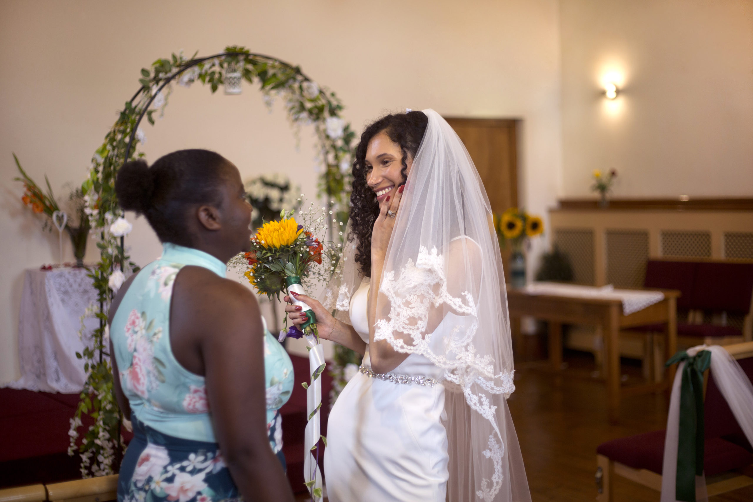 Bride and guest smiling after the church ceremony micro wedding photographer Bristol