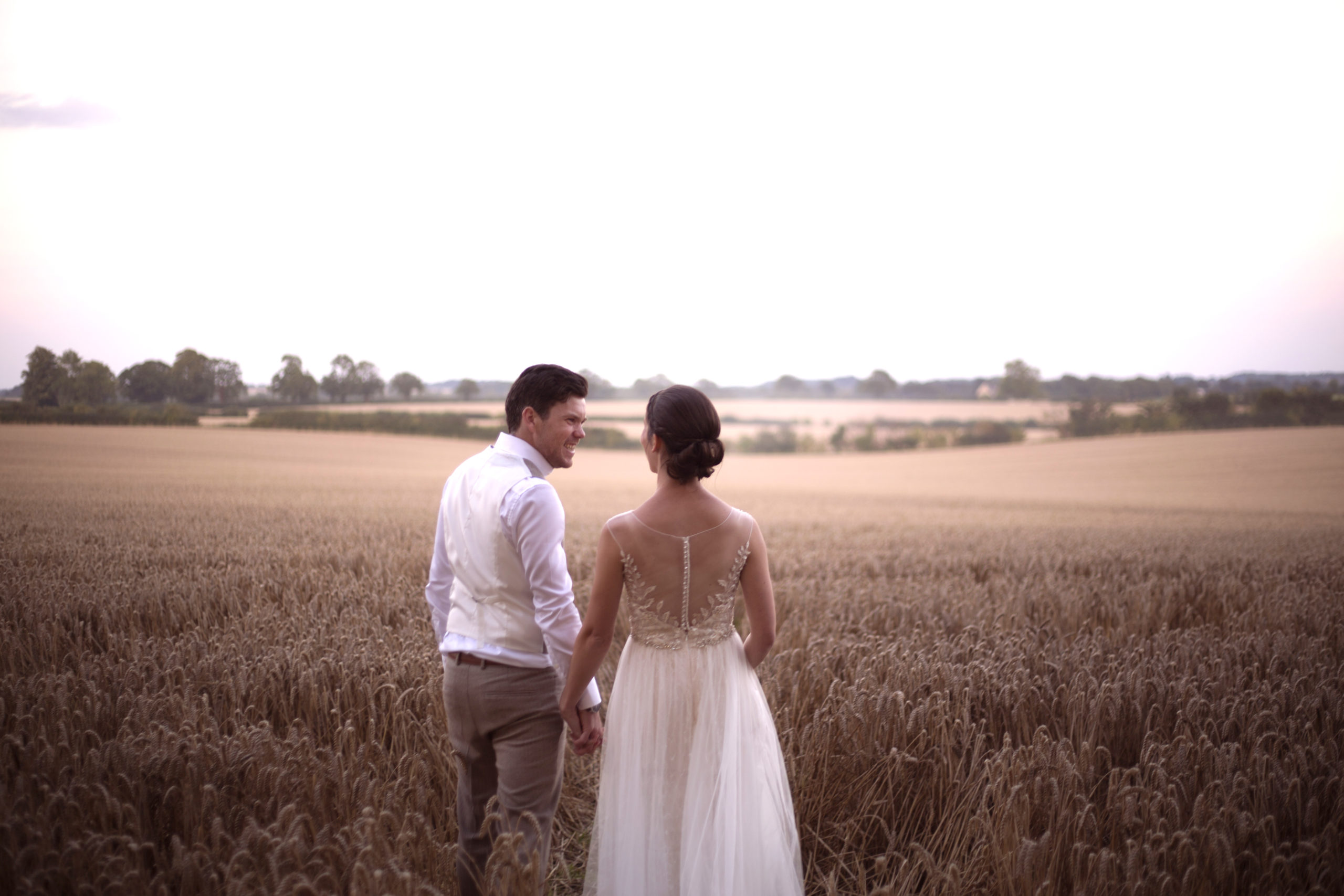 Bride and groom walking in cornfield at Cripps barn wedding photographer gloucestershire