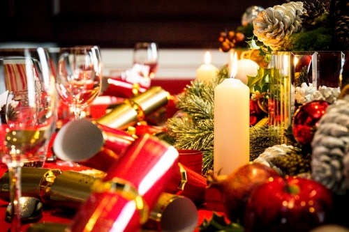 A dining table is ready for christmas lunch with decorations, place settings and candles