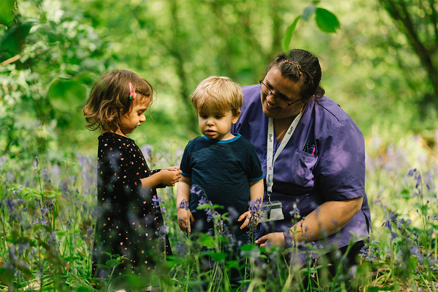 Key worker picking flowers with children.