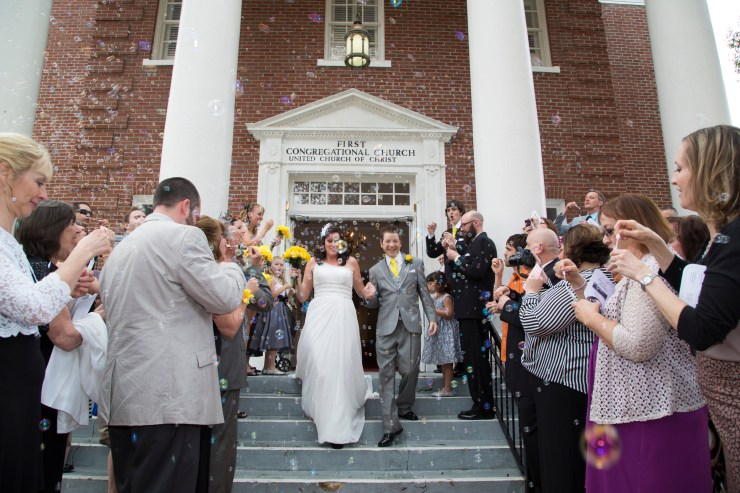 Couple leaving the church on their wedding day coming down the steps with guests on either side blowing bubbles.