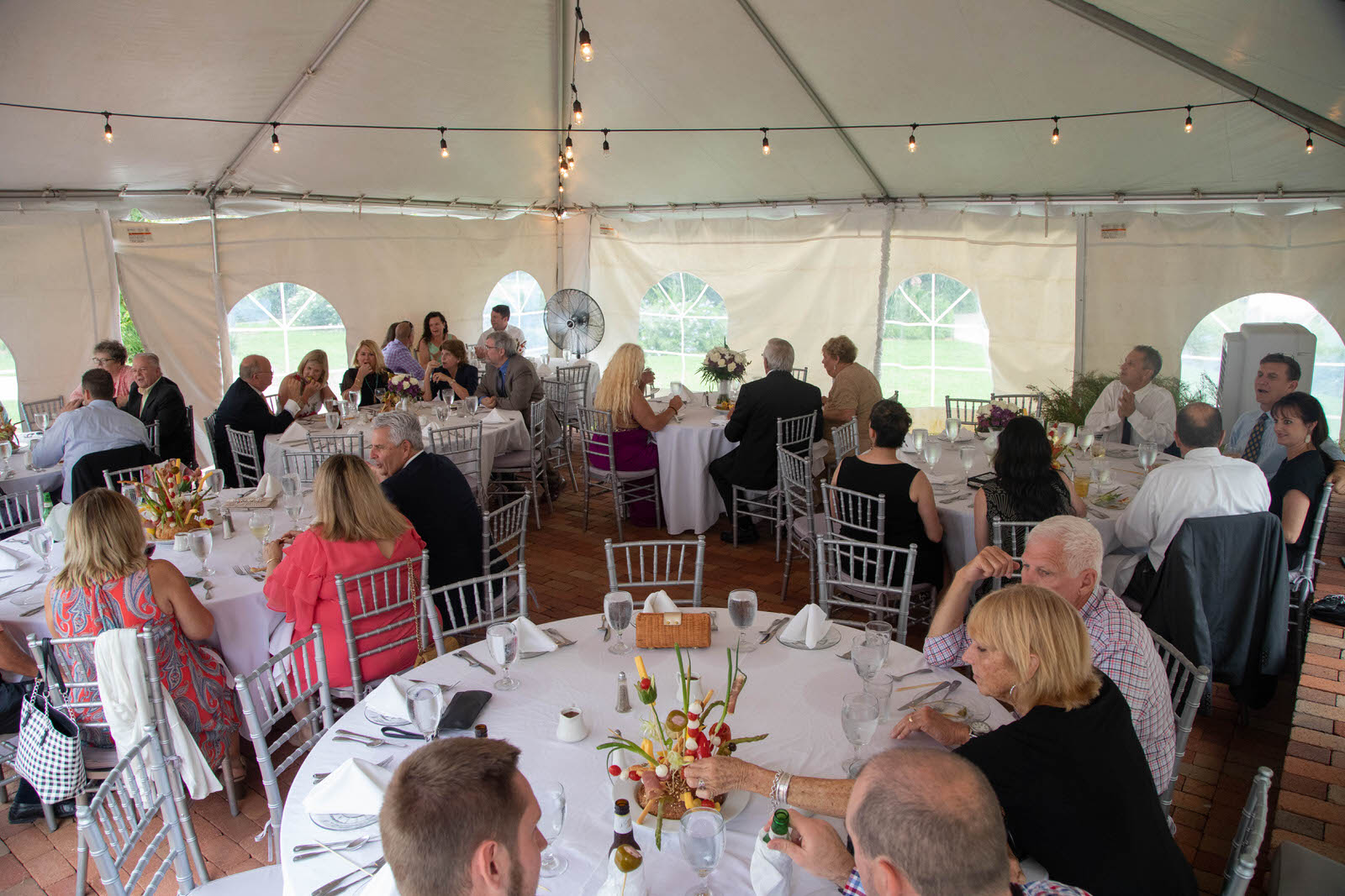 Guests enjoying a wedding reception sitting at round dinner tables in a marquee at Capen House