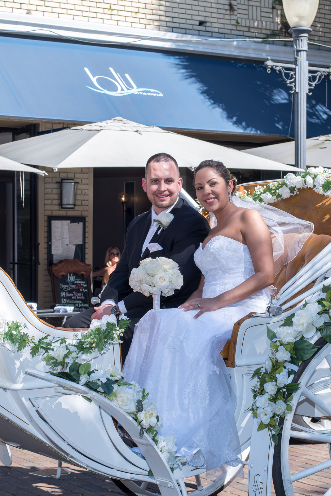 A newlywed couple pose for a photo sitting in an elegant horse drawn carriage in front of Blu restaurant on Park Avenue