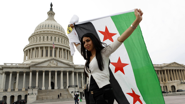 An anti-Assad protester carries the Syrian freedom flag in front of the U.S. Capitol in Washington