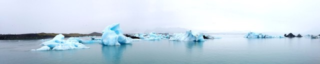 Glacial lagoon with large chunks of black and white ice floating in it and a large glacier in the background.