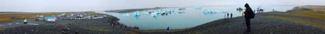 Panorama of glacial lagoon with shoreline in the foreground with various people walking around, icebergs floating in the water.