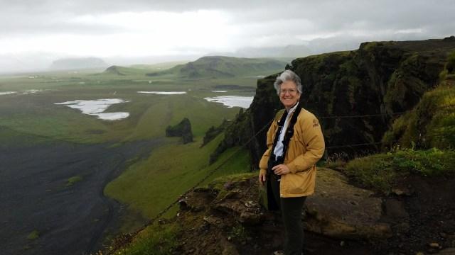 Woman with binoculars on volcanic clifftop overlooking ocean.