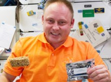 Astronaut Mike Finke eating a student-developed snack during STS-134