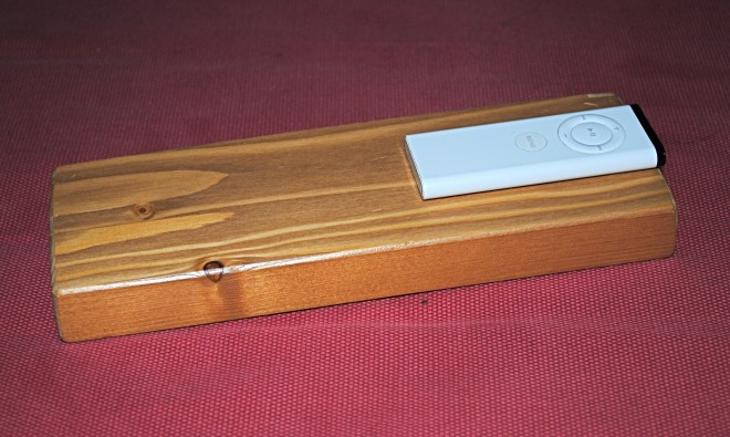 An Apple TV remote is glued to a piece of wood to prevent easy loss.