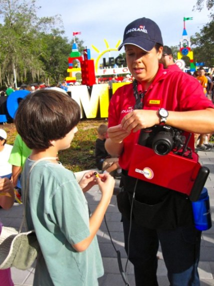 Young Lego fan trading Minifigs with a Legoland Florida Staff member