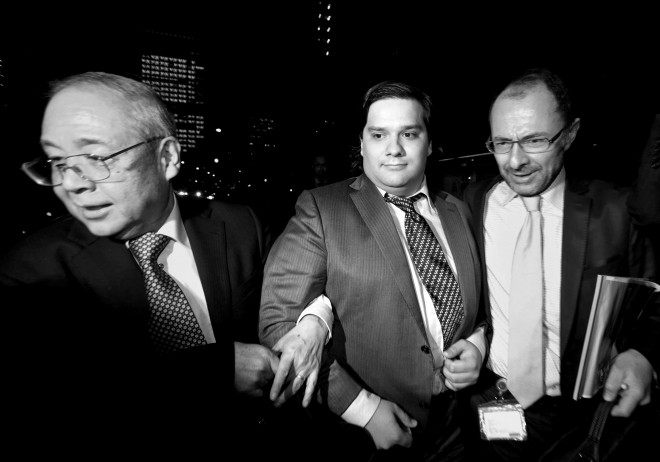 Mark Karpeles, chief executive officer of Mt. Gox, center, is escorted as he leaves the Tokyo District Court on Friday, Feb. 28, 2014. Photo: Tomohiro Ohsumi/Bloomberg via Getty Images