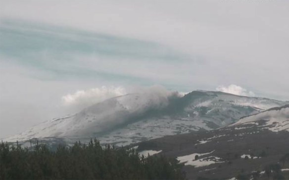 Webcam image of Copahue in Chile, seen on October 16, 2014. A small steam-and-ash plume can be seen along with deposits of fresh, dark grey across on the volcanoes slopes. Image: SERNAGEOMIN.