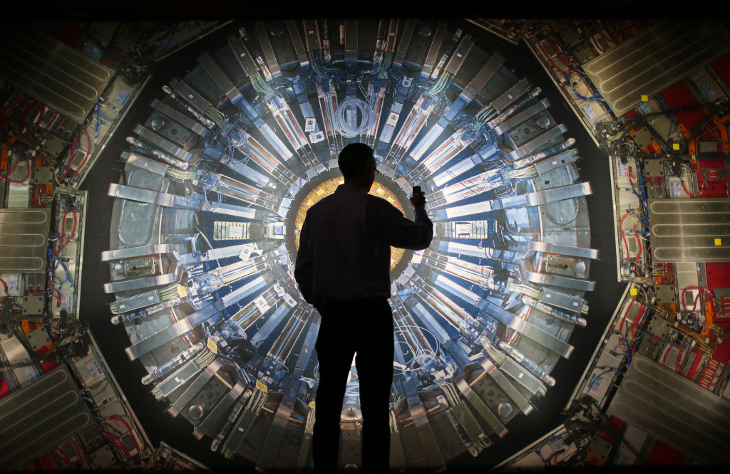A visitor stands in front of a large image of the Large Hadron Collider at the London Science Museum's 'Collider' exhibition.