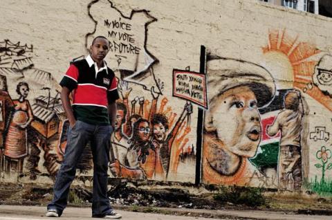 Boniface Mwangi posando delante de uno de sus murales. Fuente: Africanseer.