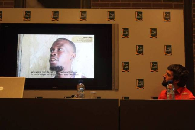 "Jordi Tomàs observa un vídeo en el Patrick Lambal explica desde Senegal porqué ha participado en el libro. Ambos firman ""El pescador que volia anar al país dels blancs""."