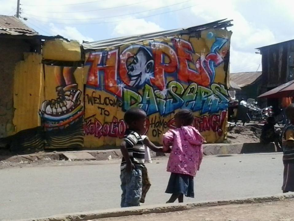 Niños de Korogocho delante de uno de los murales pintados durante el Koch Festival. Imagen cedida por Hoperaisers.