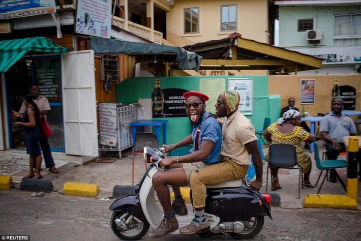 El estilista ghanés Daniel Quist (conduciendo la scooter) y el pionero de la moda DJ Evans Mireku Kissi - más conocido como Steloo-, por las calles de Accra. and Kissi go for a spin around Accra, much to the surprise of some onlookers