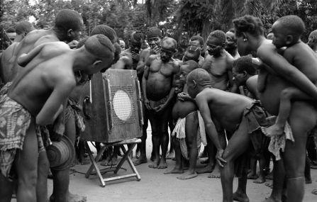 Pigmeos Batwa del Congo escuchan las grabaciones de sus canciones que les ha hecho el etnomusicólogo sudafricano Hugh Tracey, en 1958. Imagen de la International Library of African Music (ILAM).
