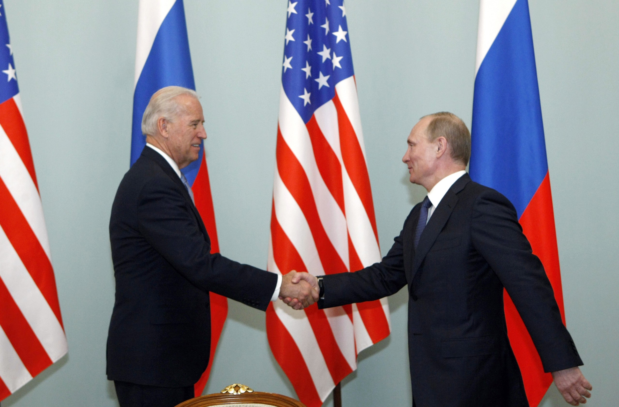 In this March 10, 2011 file photo, then U.S. Vice President Joe Biden, left, shakes hands with Russian Prime Minister Vladimir Putin in Moscow. (Alexander Zemlianichenko/AP)