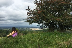 woman sitting on a hill overlooking the English countryside