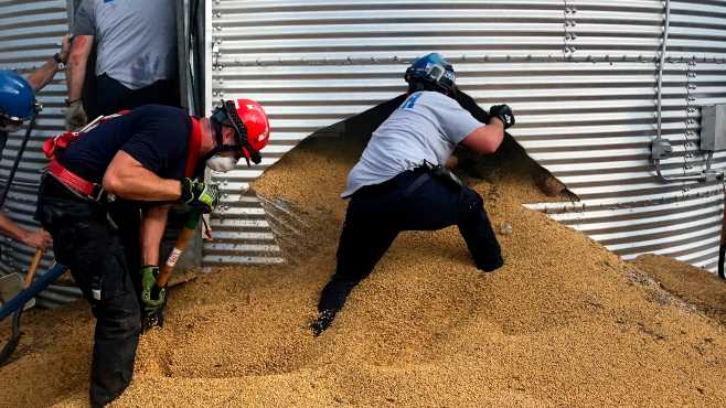 In this May 30, 2019 photo provided by the Ross Township Fire Department rescue personnel shovel soybeans out of the bottom of a bin during an effort to rescue farmer Jay Butterfield, who was buried up to his neck inside. He became buried up to his neck while trying to break up clumps of soybeans in the bin on his farm in Ross Township, Ohio