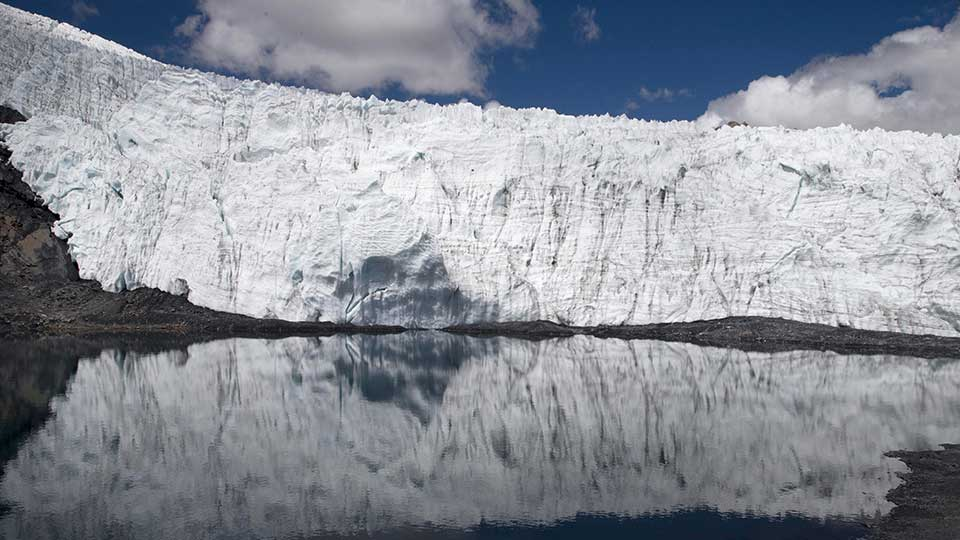 In this Aug. 12, 2016 photo, the Pastoruri glacier is reflected in a lagoon in the Huascaran National Park in Huaraz, Peru.