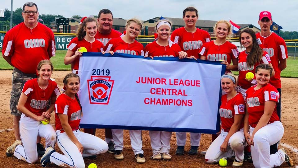Canfield/Poland Little League Junior Softball Team holding a banner for winning the Central Region Championship.