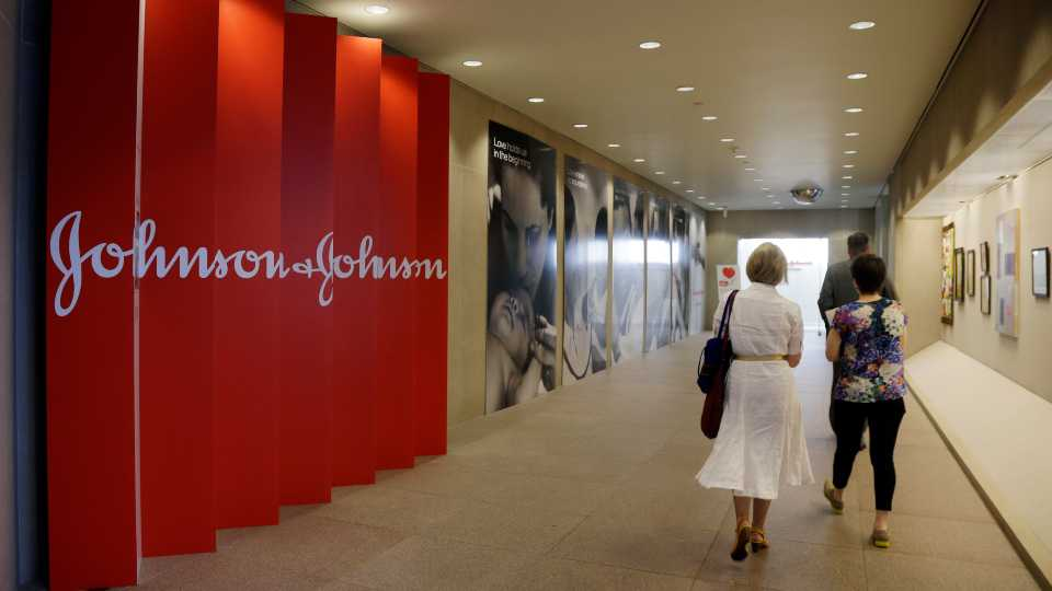In this July 30, 2013, file photo, people walk along a corridor at the headquarters of Johnson & Johnson in New Brunswick, N.J. A cheaper version of J&J's top-selling drug, the rheumatoid arthritis treatment Remicade, could be available in the U.S. two years early after a federal judge ruled a key patent on the drug invalid. J&J said Wednesday, Aug. 17, 2016, it plans to appeal the ruling.