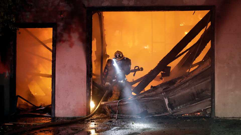 A firefighter works the scene of a wildfire-ravaged home Thursday, Oct. 24, 2019, in Santa Clarita, Calif. Fast-growing fires across California have forced thousands of people to evacuate as dry winds and high heat feed the flames.