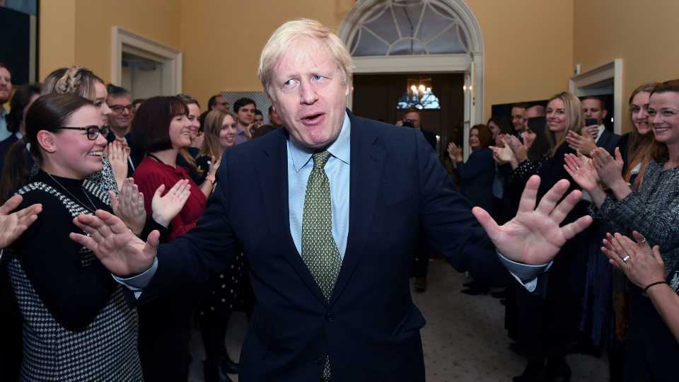 Britain's Prime Minister Boris Johnson is greeted by staff as he returns to 10 Downing Street, London, after meeting Queen Elizabeth II at Buckingham Palace and accepting her invitation to form a new government, Friday Dec. 13, 2019. Boris Johnson led his Conservative Party to a landslide victory in Britain's election that was dominated by Brexit.
