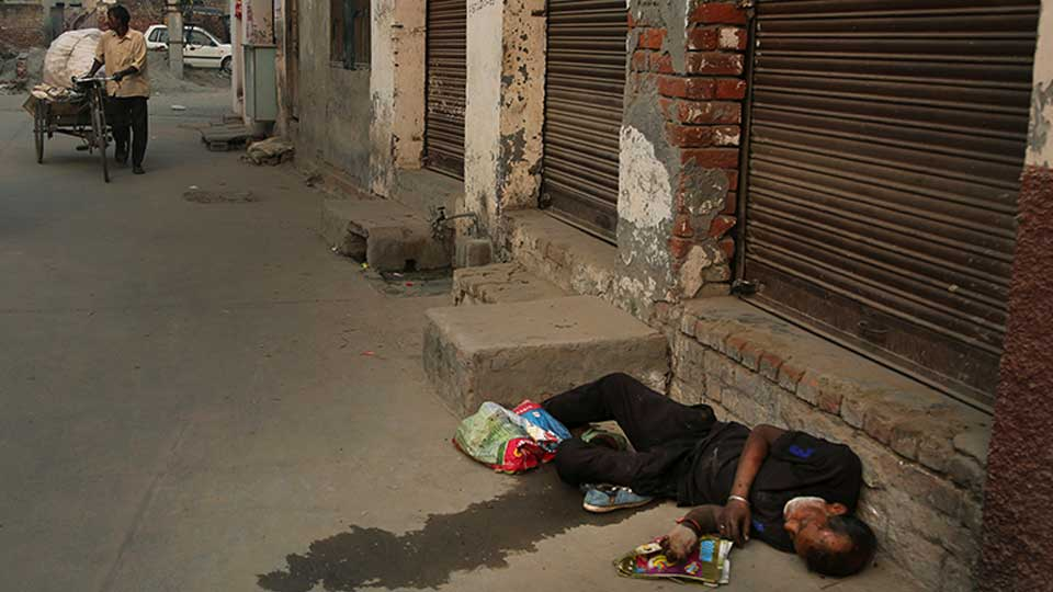 In this Oct. 31, 2019, photo, an Indian drug user lies unconscious by the side of a road in Kapurthala, in the northern Indian state of Punjab. Mass abuse of the opioid tramadol spans continents, from India to Africa to the Middle East, creating international havoc some experts blame on a loophole in narcotics regulation and a miscalculation of the drug's danger. Punjab, the center of India's opioid epidemic, was among the latest to crack down on the tramadol trade. Researchers estimate about 4 million Indians use heroin or other opioids, and a quarter of them live in the Punjab, India's agricultural heartland bordering Pakistan.