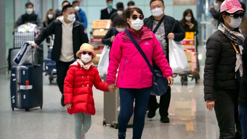 Travelers wearing face masks walk through the international arrivals area at Beijing Capital International Airport