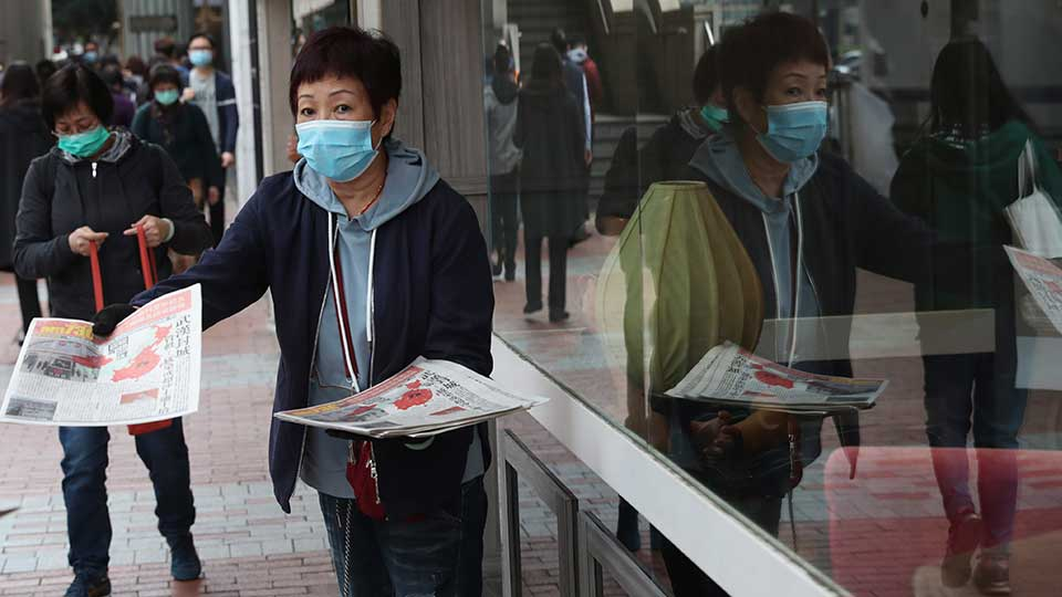 A women wearing a protective face mask delivers a leaflet on coronavirus in Wuhan, in Hong Kong, Friday, Jan 24, 2020. China broadened its unprecedented, open-ended lockdowns to encompass around 25 million people Friday to try to contain a deadly new virus that has sickened hundreds, though the measures' potential for success is uncertain.