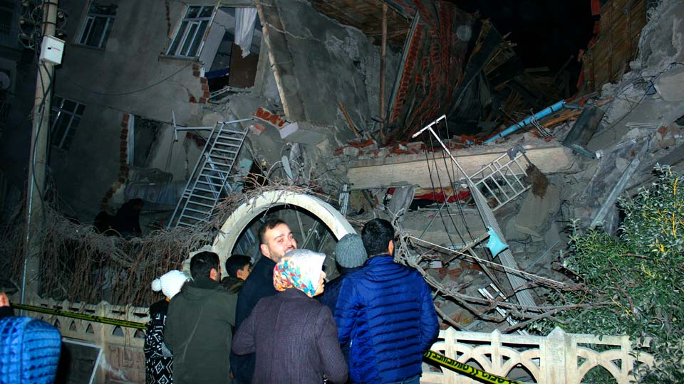 People look at a collapsed building after a 6.8 earthquake struck Elazig city centre in the eastern Turkey