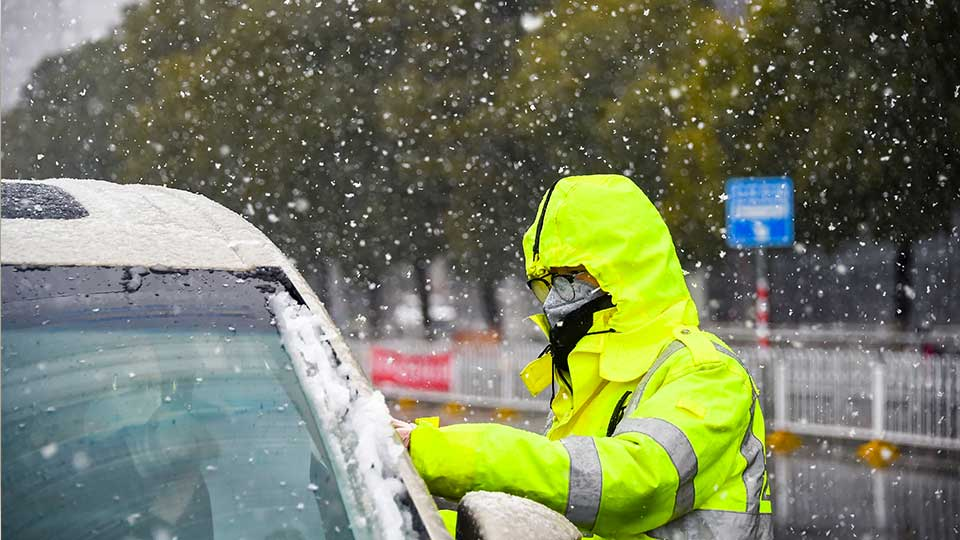 In this photo released by China's Xinhua News Agency, a traffic policeman wearing a face mask checks a car during a snowfall in Xiaogan in central China's Hubei Province, Saturday, Feb. 15, 2020. The virus is thought to have infected more than 67,000 people globally and has killed at least 1,526 people, the vast majority in China, as the Chinese government announced new anti-disease measures while businesses reopen following sweeping controls that have idled much of the economy.