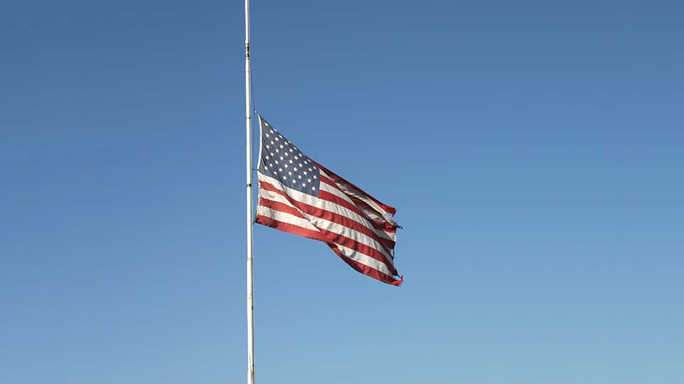 An American flag being flown at half staff.