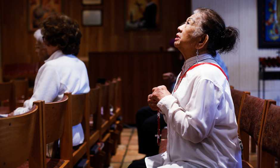Esther Gianan, of Tampa, a retired registered nurse, prays for those who are affected by the coronavirus during Mass at St. Lawrence Catholic Church in Tampa, Fla., Friday, March 6, 2020. (