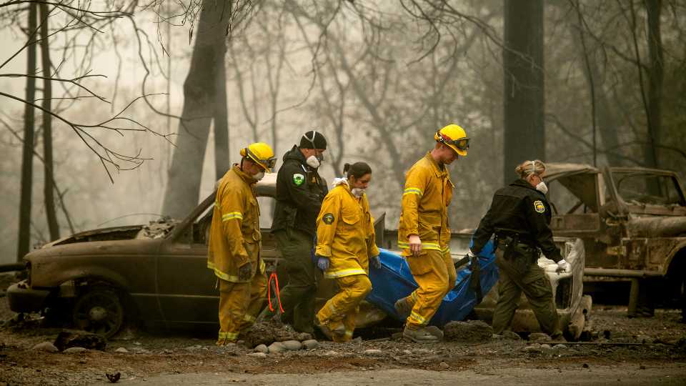 In this Nov. 14, 2018, file photo, firefighters and deputies carry the body of a Camp Fire victim at the Holly Hills Mobile Estates in Paradise, Calif. Pacific Gas & Electric said Monday, March 23, 2020, it will plead guilty to 84 counts of involuntary manslaughter in connection with the 2018 fire in Northern California that killed 84 people and decimated three towns