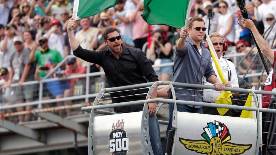 In this May 26, 2019, file photo, actors Christian Bale, left, and Matt Damon wave green flags to start Indianapolis 500 IndyCar auto race at Indianapolis Motor Speedway in Indianapolis. The Indianapolis 500 scheduled for May 24 has been postponed until August because of the coronavirus pandemic and won't run on Memorial Day weekend for the first time since 1946. The race will instead be held Aug. 23.