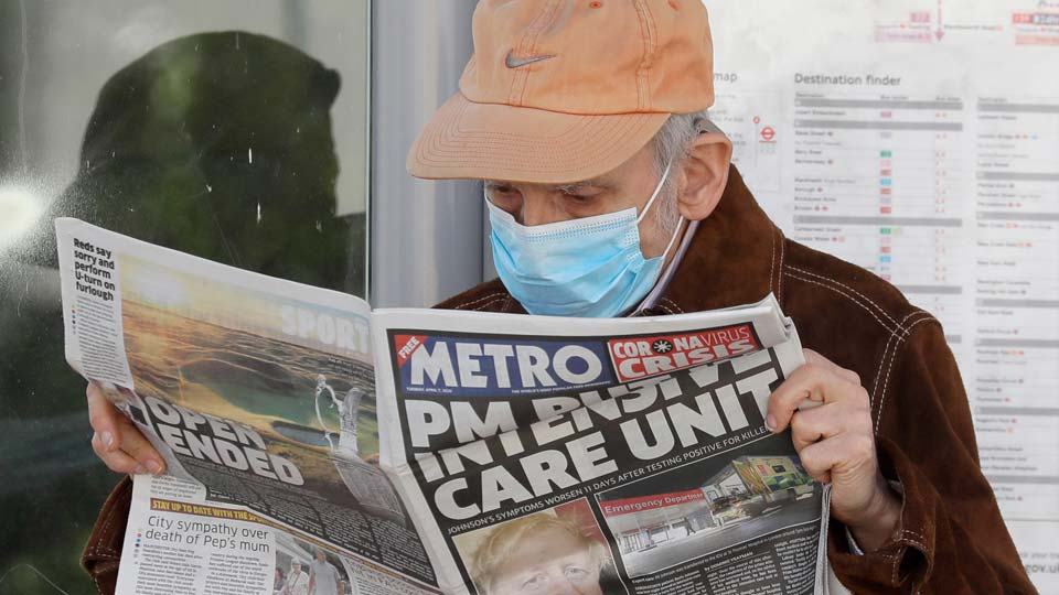 A man reads a newspaper with the headline: 'PM in intensive care', outside St Thomas' Hospital in central London