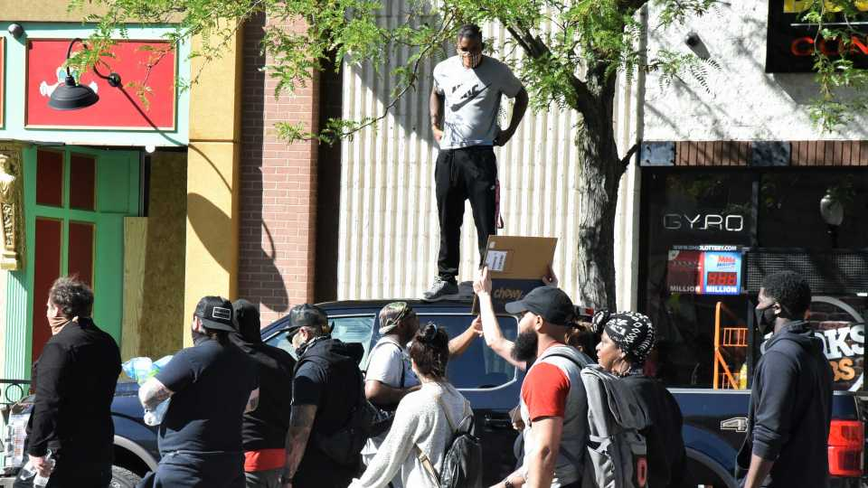 Man stands on car over marching crowd