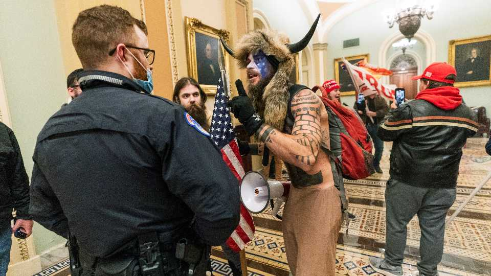 FILE - In this Jan. 6, 2021, file photo supporters of President Donald Trump are confronted by U.S. Capitol Police officers outside the Senate Chamber inside the Capitol in Washington. An Arizona man seen in photos and video of the mob wearing a fur hat with horns was also charged Saturday in Wednesday's chaos. Jacob Anthony Chansley, who also goes by the name Jake Angeli, was taken into custody Saturday, Jan. 9.