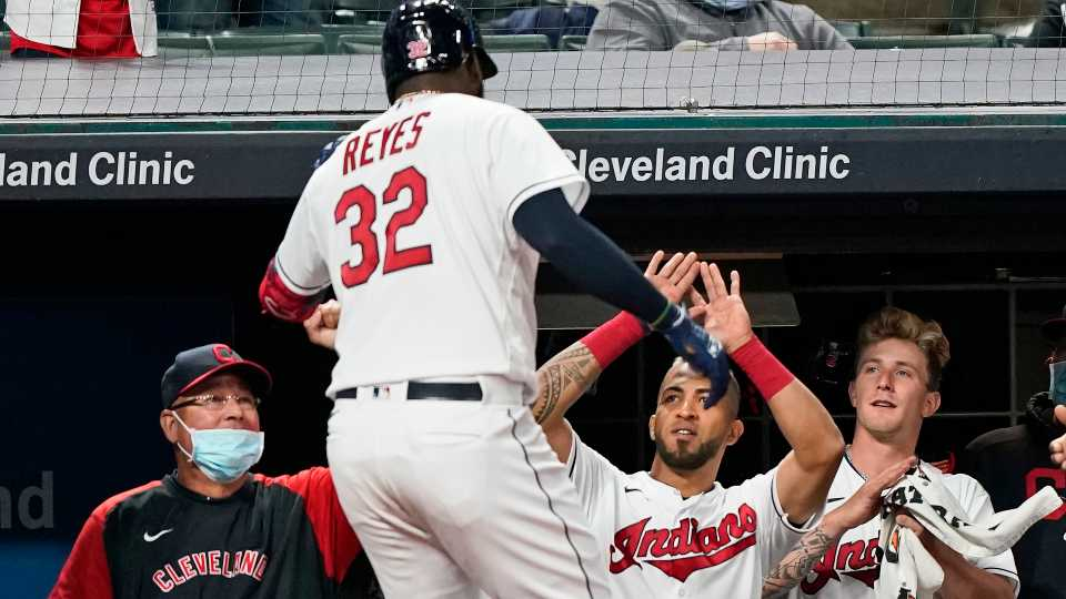 Cleveland Indians' Franmil Reyes (32) is congratulated by teammates after hitting a solo home run during the sixth inning in a baseball game against the Detroit Tigers, Friday, April 9, 2021, in Cleveland. The Indians won 4-1.